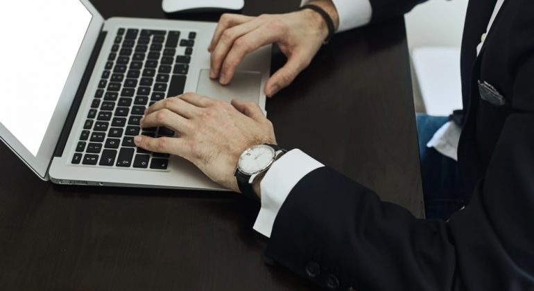 Cropped image of a young man working on his laptop , rear view of business man hands busy using laptop at office desk, young male student typing on computer sitting at wooden table